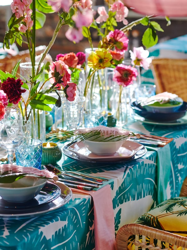 Partie d'une table dressée et décorée avec des assiettes FORMIDABEL, des textiles à motifs audacieux, des fleurs et des feuilles artificielles.