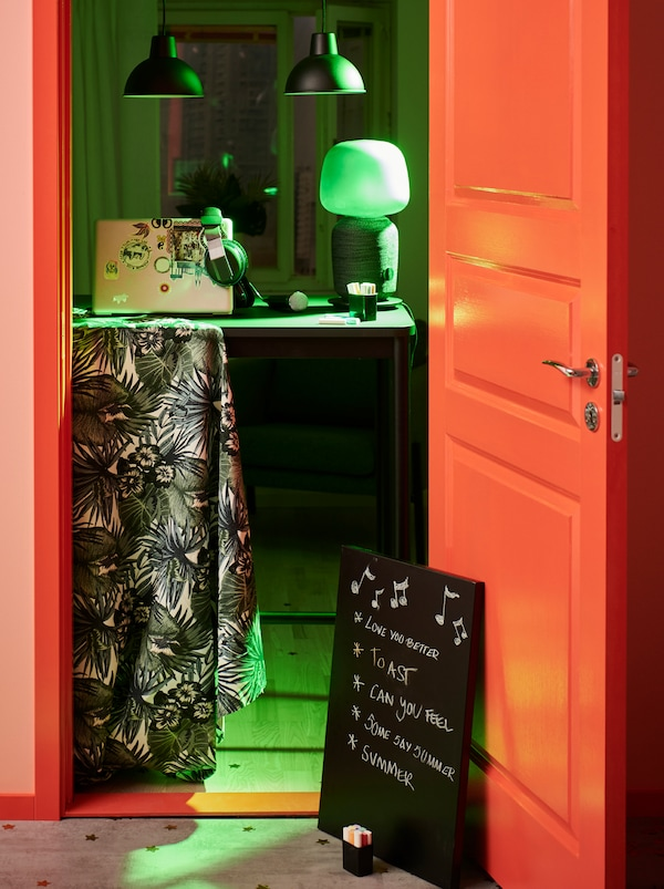Party-lit room with DJ accessories on a TOMMARYD table across the doorway. A memo board on the floor lists musical wishes.