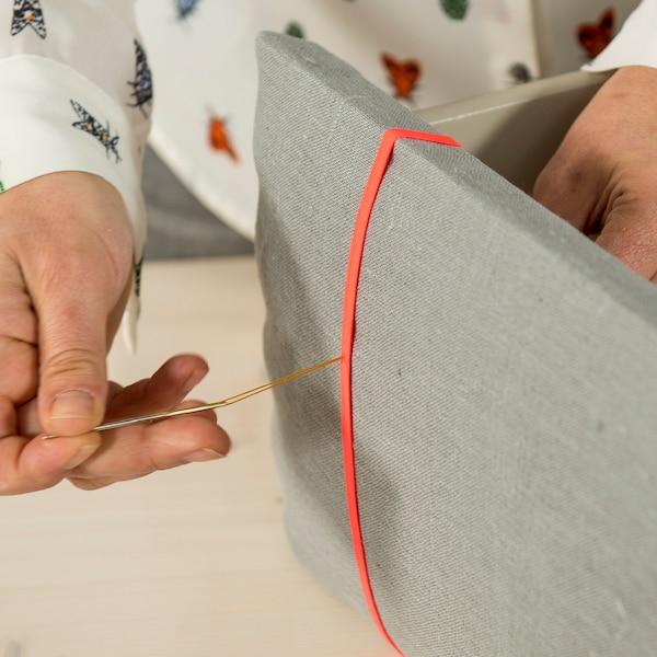Passez un peu de soie de couture dans une aiguille solide, en l'insérant de l'intérieur vers l'extérieur par le trou de la façade du tiroir.