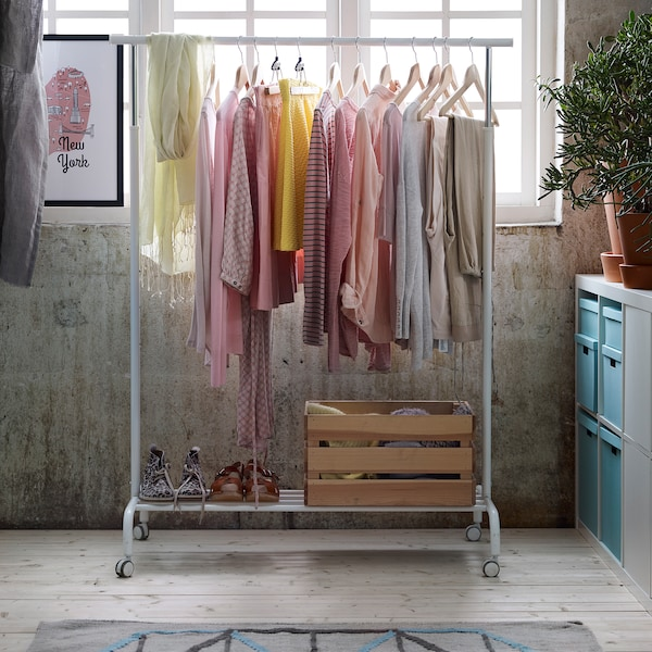 Pastel coloured clothing hanging from a white RIGGA clothing rack in a light-filled room.
