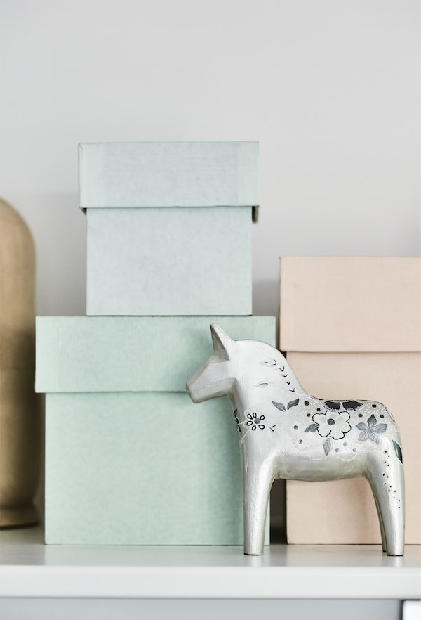 Pastel storage boxes stacked on a shelf.
