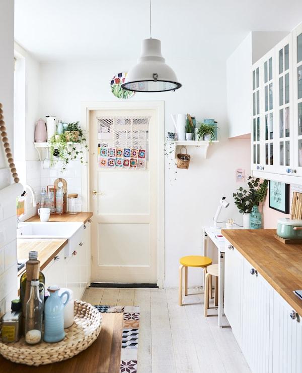 パステルカラーの備品をそなえた白いキッチン。