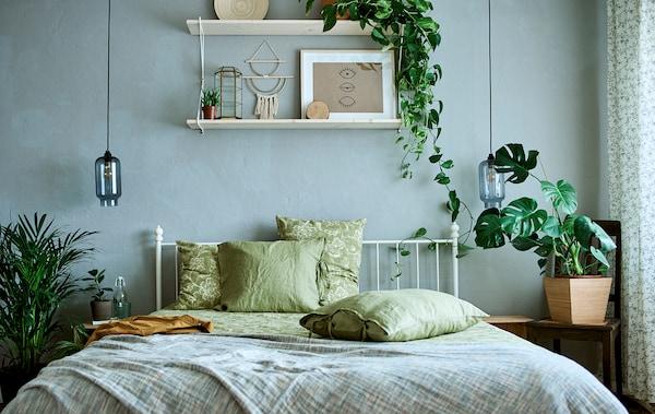 Pat alb, cu un cadru metalic și lenjerie de pat verde, simplă și cu imprimeuri, într-o cameră cu plante și lucrări de artă.