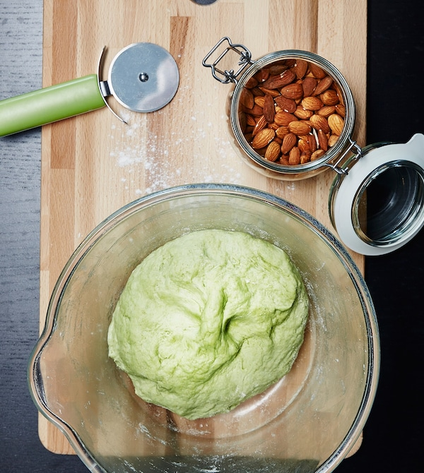 Pâte à biscuits verte dans un bol en verre sur une planche à découper