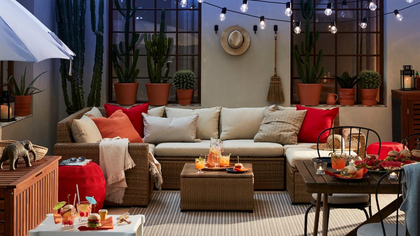 Patio avec canapé d'extérieur, petite table blanche et tabourets, table avec chaises et parasol.