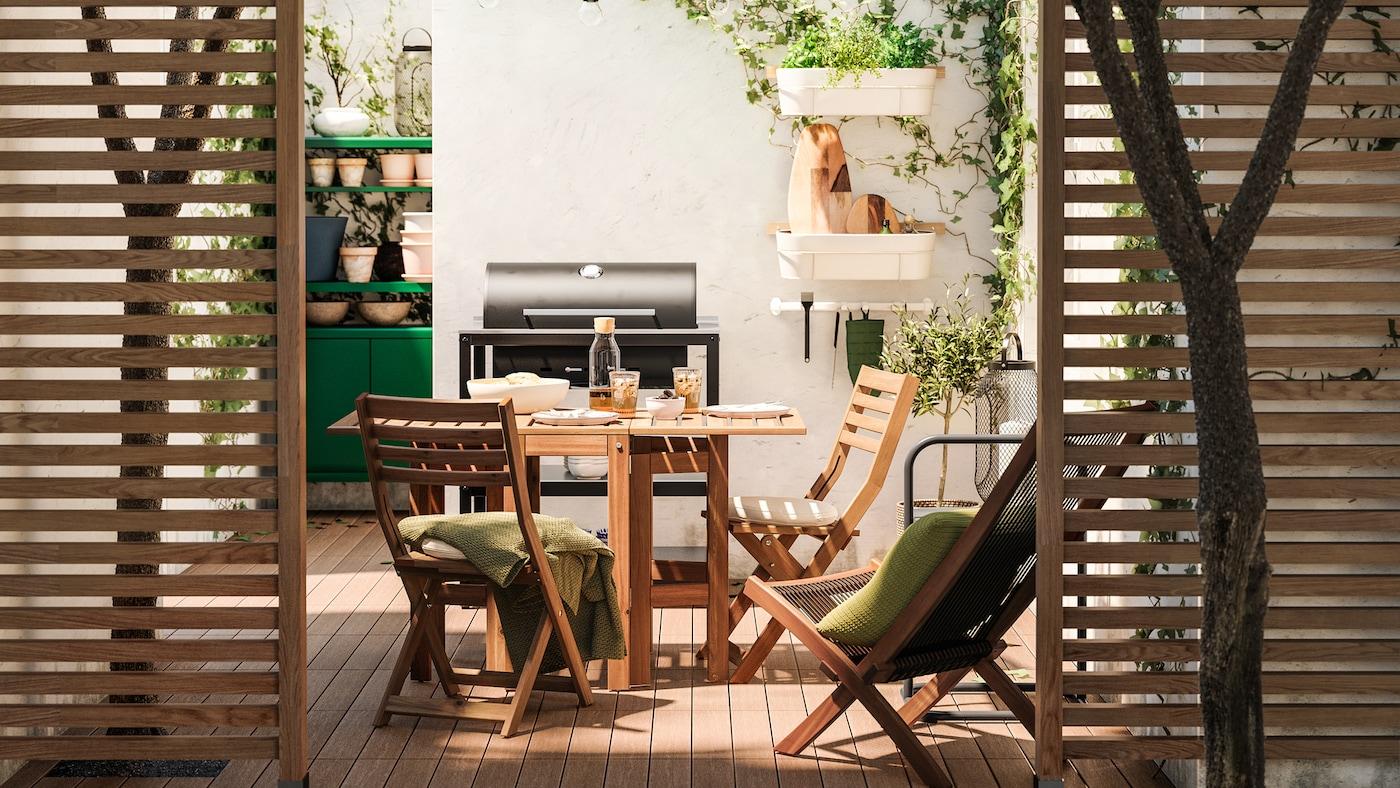 Patio dall'atmosfera rilassante, con tavolo e sedie in legno, grill nero, pavimento effetto legno e rampicanti.