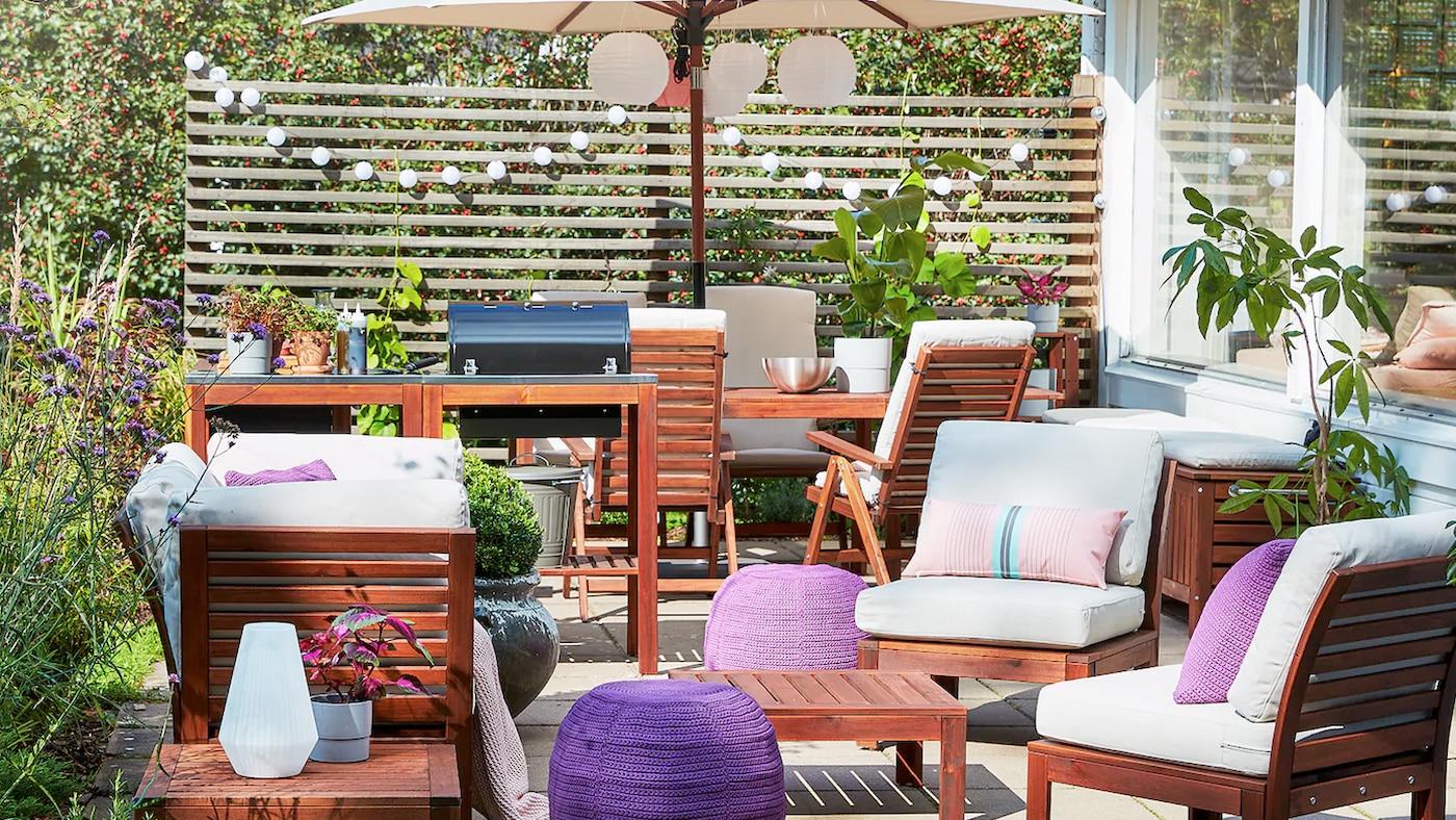 Patio met een barbecue, een tuinset voor 4 personen in acacia, een beige parasol, paarse poefs en beige buitenkussens.