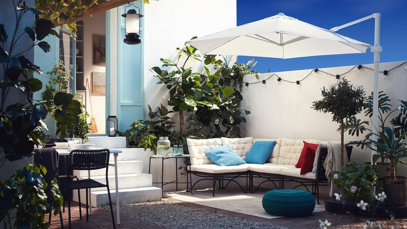 Patio z sofą modułową, na której leżą białe poduszki, białym parasolem, niebieskozielonym pufem i mnóstwem roślin.