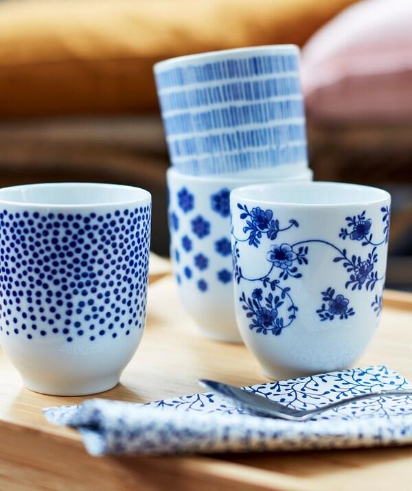 Patru căni de ceai mici albe cu diferite modele albastru închis.