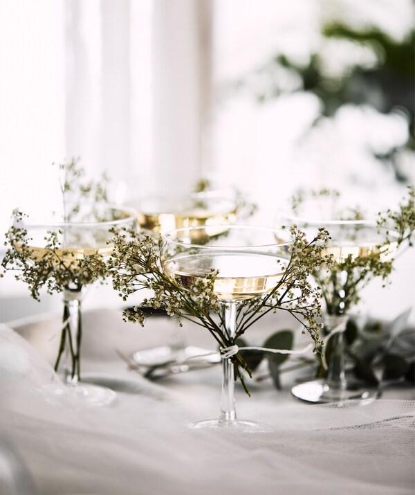 Patru cupe STORHET pentru șampanie pe o tavă, cu crenguțe de flori sălbatice prinse de picioarele de sticlă.