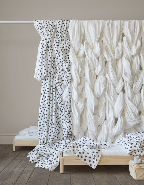 Patterned and plain fabric hanging in plaits over a curtain rod.