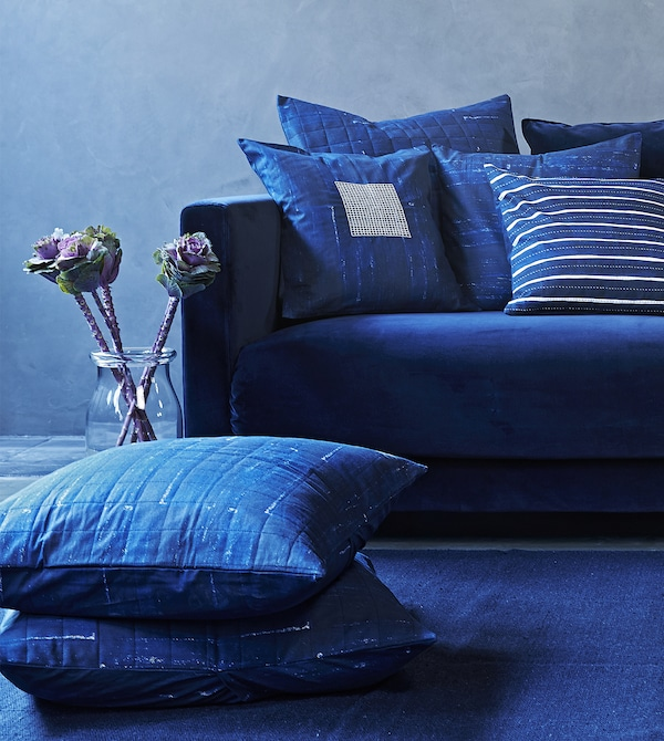 Patterned blue cushions on a blue sofa.