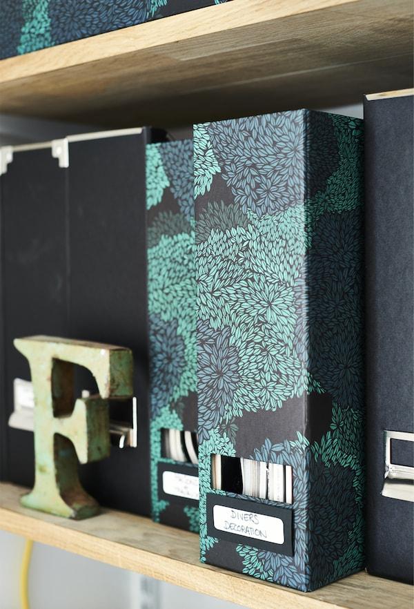 Patterned box files on a shelf.