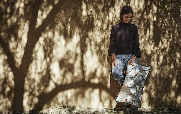 Paulin Machado holding a cushion with cactus print.