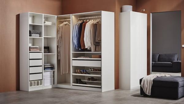 PAX-kaappikokonaisuus jossa on vaatteita henkareissa, viikattuna hyllyillä sekä useampi vetolaatikko.