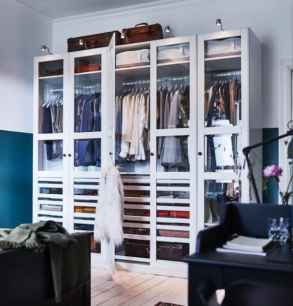 pax/tyssedal kledingkastcombinatie met wit glazen deuren, gevuld met kledij