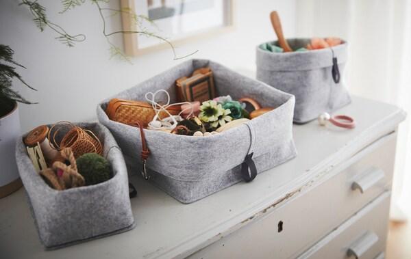 Pe o comodă veche și uzată este așezat un set de coșuri RAGGISAR din materiale textil pline cu bijuterii și mărunțișuri.
