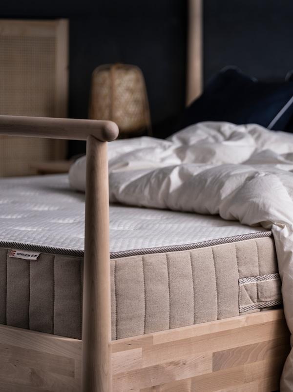 Pe un pat GJÖRA din lemn de mesteacăn aflat într-un dormitor luminat subtil se află o saltea VATNESTRÖM și o pilotă, ambele fără lenjerie de pat.