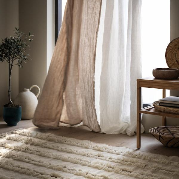 PEDERSBORG matta ligger framför ett fönster där det hänger en gardin som fladdrar i vinden.