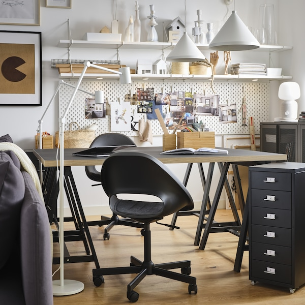 Pegboards, two pendant lamps and floor lamps in white, a table and a drawer unit in black and two black swivel chairs.