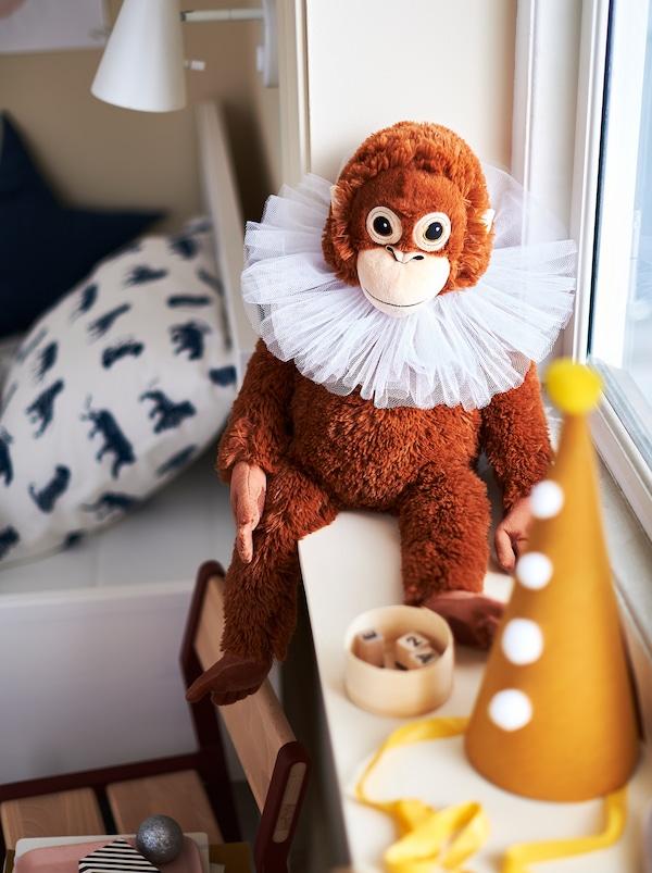 Peluche singe DJUNGELSKOG brun et son chapeau doré posés sur le rebord de la fenêtre dans une chambre d'enfant à thématique decirque.