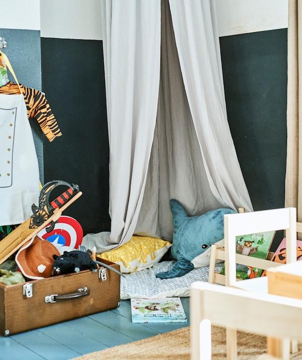 Peluches et coussins sous un ciel de lit à côté d'une valise remplie de jouets.