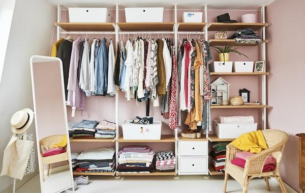 Penderie ouverte remplie de vêtements avec tringles, tablettes et boîtes, sur fond de mur rose.