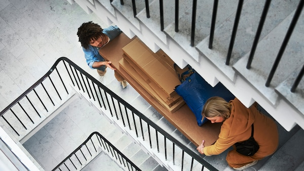 People carry boxes with ikea products up stairs