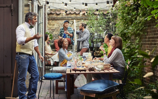 People sitting and standing around a wooden table in a backyard area with brick walls and plants.