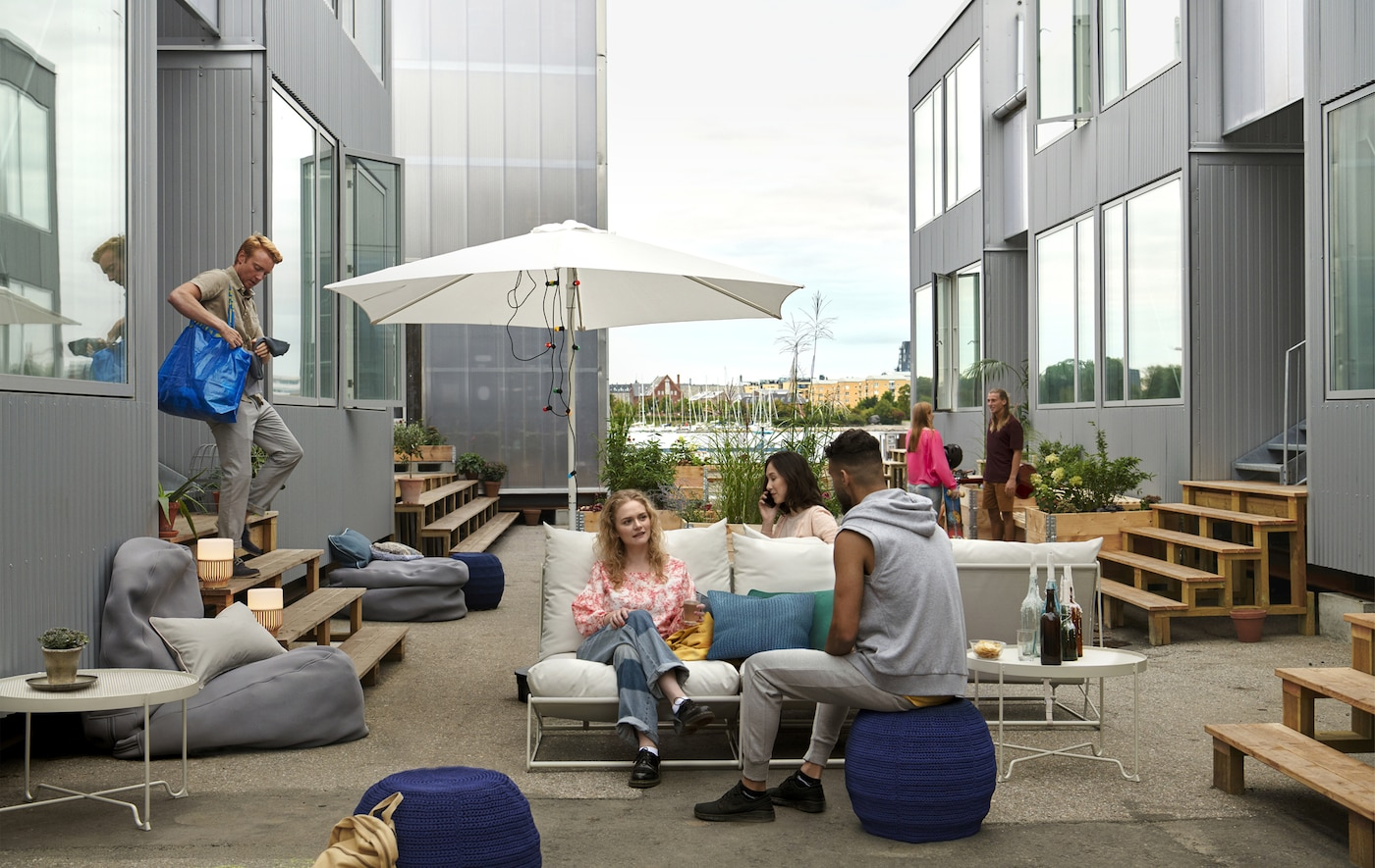People sitting on sofas and floor cushions with an umbrella and side tables in an outdoor area between shipping container homes.