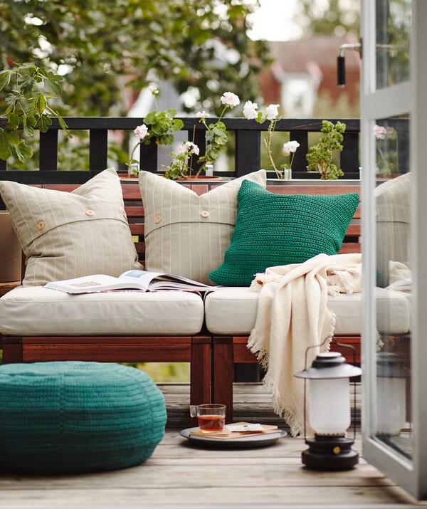 Pequeno-almoço na varanda, com as portas abertas e muitas almofadas, mantas e alguns móveis para exterior.