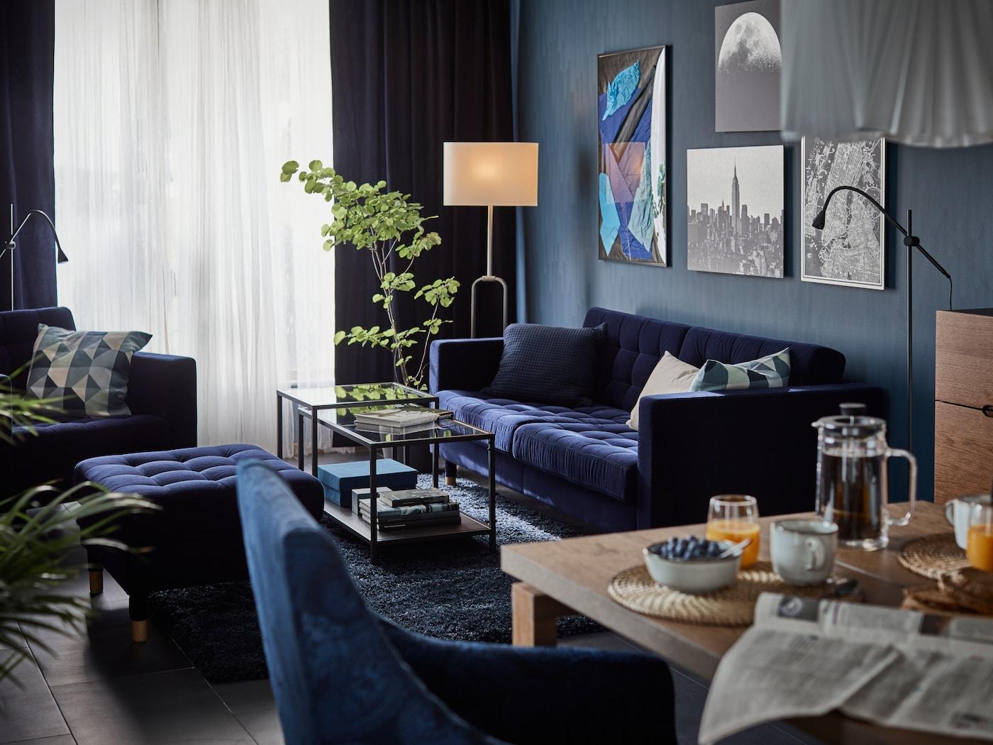 Pequeno estúdio com sofá-cama de 2 lugares Vansbro verde forte, têxteis em preto e branco, estantes em branco e uma poltrona.