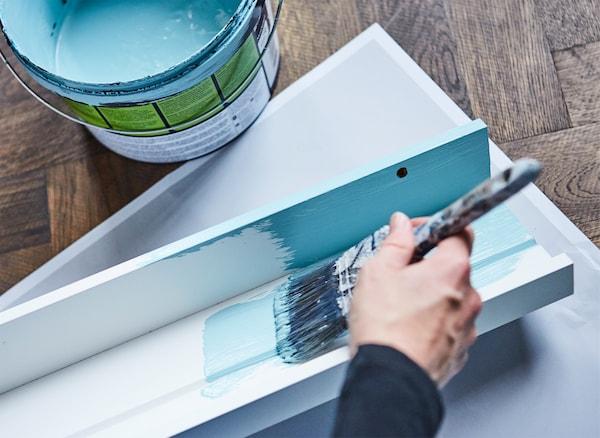 Per creare un effetto d'impatto esponi le tue foto su un paio di mensole per quadri verniciate nello stesso colore della parete. Prova le mensole per quadri MOSSLANDA di IKEA: noi le abbiamo verniciate di un turchese deciso in tinta con i colori del soggiorno.