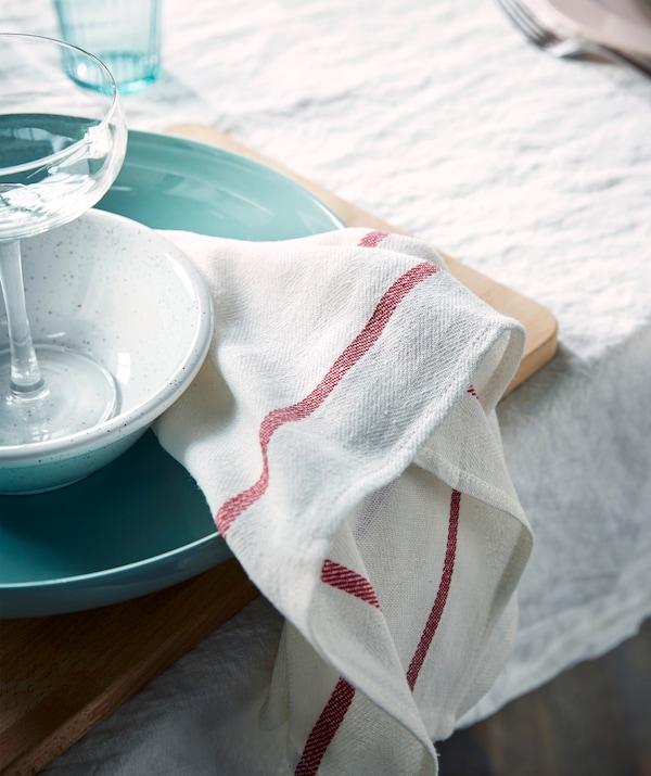 Per una tavola più accogliente usa degli strofinacci al posto dei tovaglioli di carta, come TEKLA, lo strofinaccio bianco e rosso di IKEA