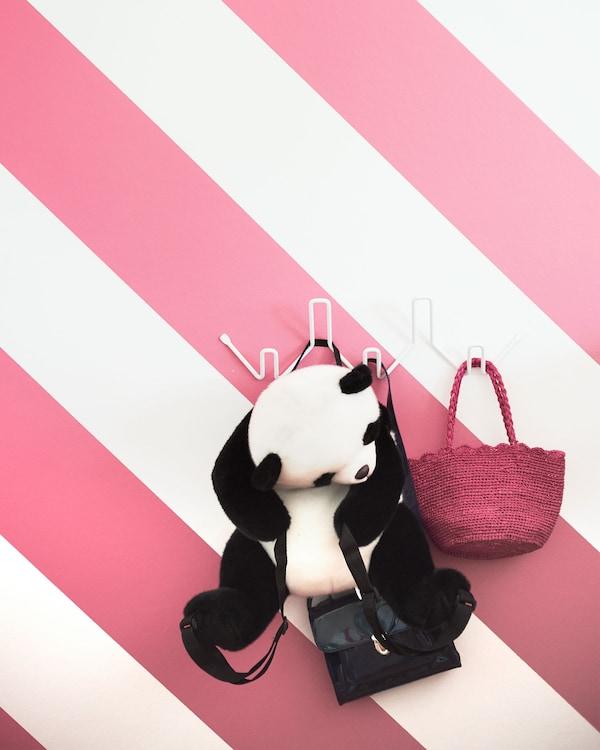 Perchero blanco montado en una pared de rayas rosas y blancas del que cuelgan un bolsito rosa y un panda de peluche.
