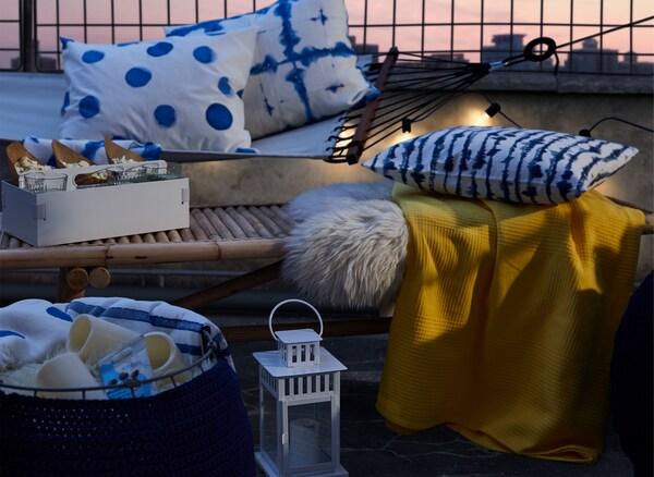 Перевернутый полый пуф с пледами и светодиодными свечами рядом с журнальным столиком и гамаком, так же заполненными пледами.