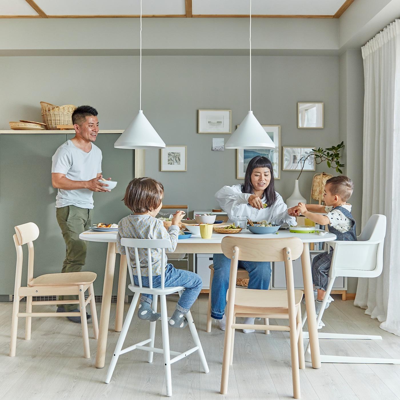 Perheen ruokailutila. Äiti ja lapset istuvat pöydän ääressä ja isä tuo tarjoilukulhoa pöytään.