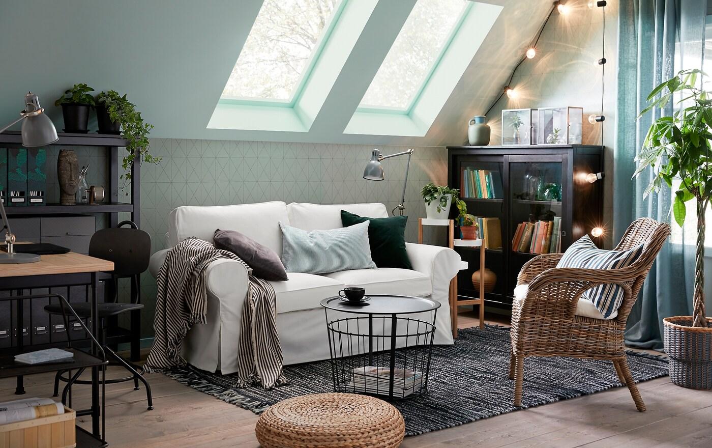 Perinteinen kahden istuttava EKTORP-sohva, jossa on valkoinen Vittaryd-päällinen. BYHOLMA/MARIEBERG-korituoli. Pieni ja kodikas vihreä, harmaa ja valkoinen olohuone, jossa on taitekatto.