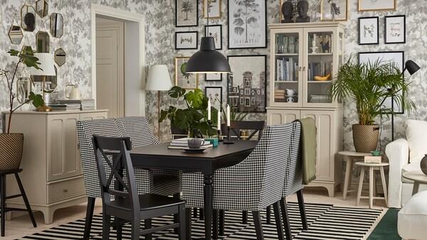 Perinteiseen tyyliin sisustettu ruokailutila, jossa musta pöytä, vaalean beiget kaapit, mustavalkoiset, käsinojalliset tuolit ja mustavalkoraidallinen matto.