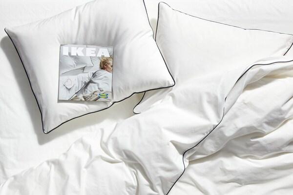 Perne albe pe un pat cu așternuturi albe și un exemplar al catalogului IKEA așezat pe una dintre perne.