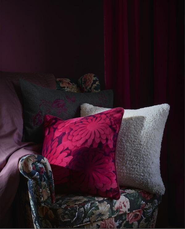 Perne de canapea cu model pe un fotoliu de culoare închisă cu motive florale pe fundal roșu închis.