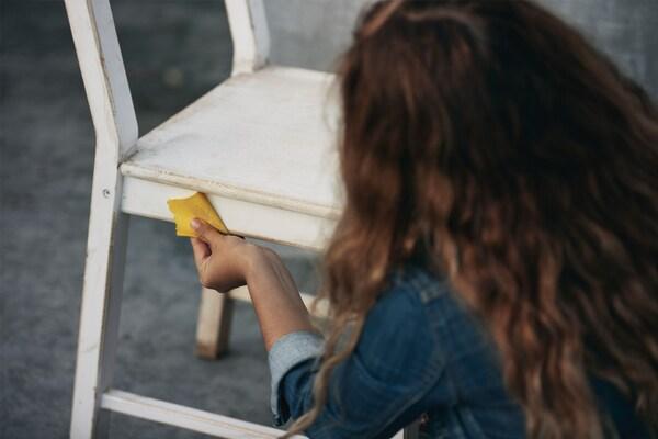 Persoană cu părul lung, șaten, care folosește șmirghel pentru a șlefui un scaun din lemn vopsit în alb, așezat pe o podea gri.