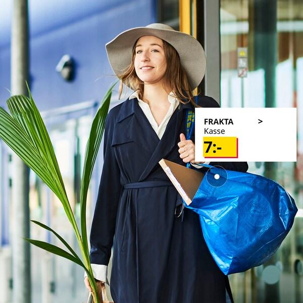 Person håller i en FRAKTA kasse och en planta utanför ett iKEA varuhus.