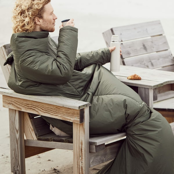 Person in a sleeping bag drinking from a travel mug