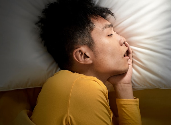 Person in a yellow shirt sleeping with their head on a pillow