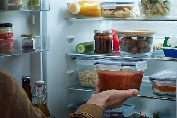 Person placing a glass IKEA 365+ food container filled with tomato sauce into a well-stocked fridge.