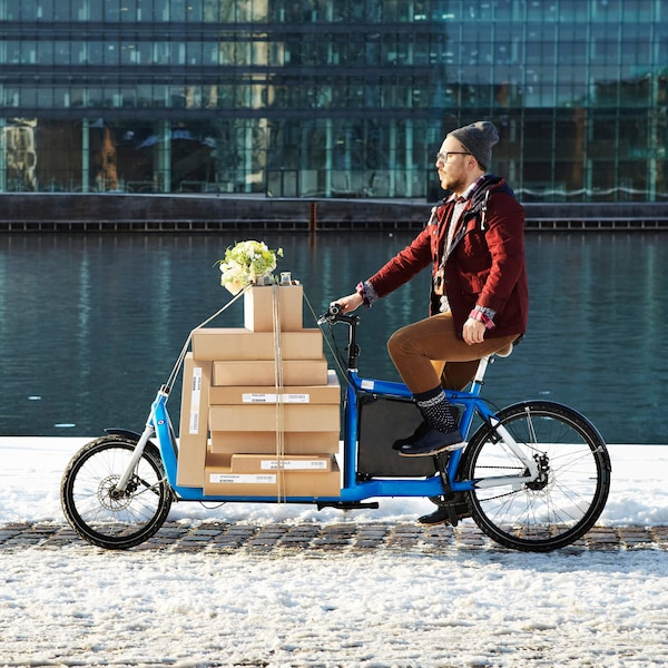 Person riding a bike carrying packages.