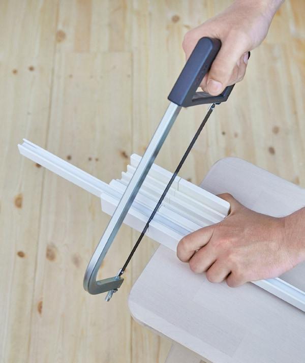 Persona cortando los rieles VIDGA a la longitud adecuada con una sierra de arco.