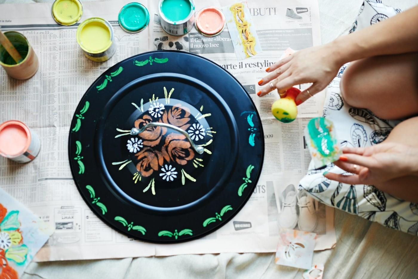 Persona decorando con colores la tapa de un cubo de basura.