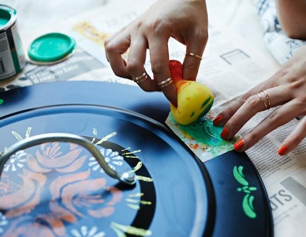 Persona decorando la tapa de un cubo de basura.